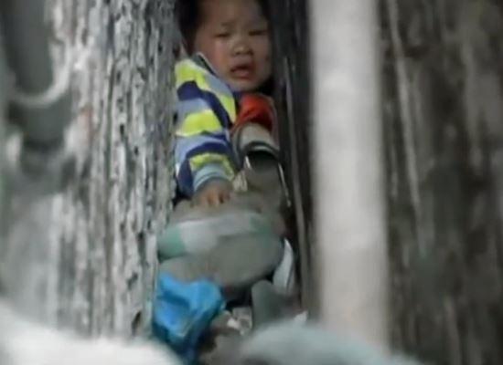 Garoto de 5 anos foi resgatado após ficar preso no espaço minúsculo entre dois prédios
