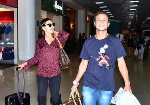 Com botas acima dos joelhos e bolsa de grife, Isis Valverde embarca no Rio