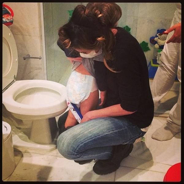 Equipada com máscara, Luciana Gimenez ajuda o filho caçula a ir ao banheiro