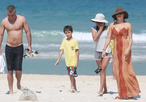 De vestido longo e biquíni da mesma estampa, Grazi curte praia com atriz