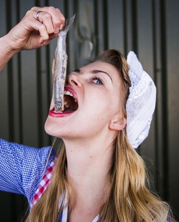 Mulher come arenque cru antes de leilão de peixes na Holanda