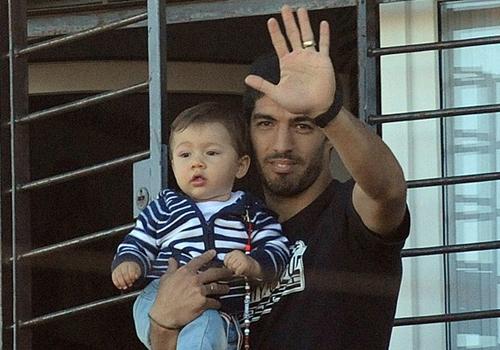 Com os filhos no colo, Suárez acena para uruguaios de casa