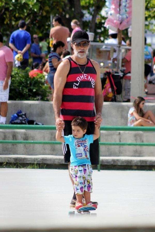 De barba grisalha, Eduardo Moscovis ensina o filho a andar de skate