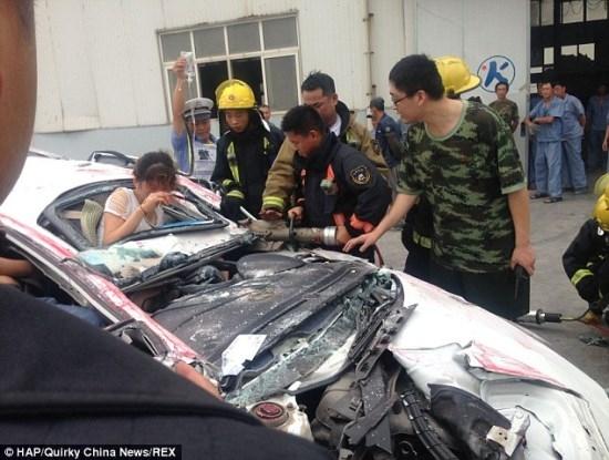 Mulher sobrevive e d sinal de 鍍udo bem com a m縊 ap um cont麒ner achatar completamente seu carro