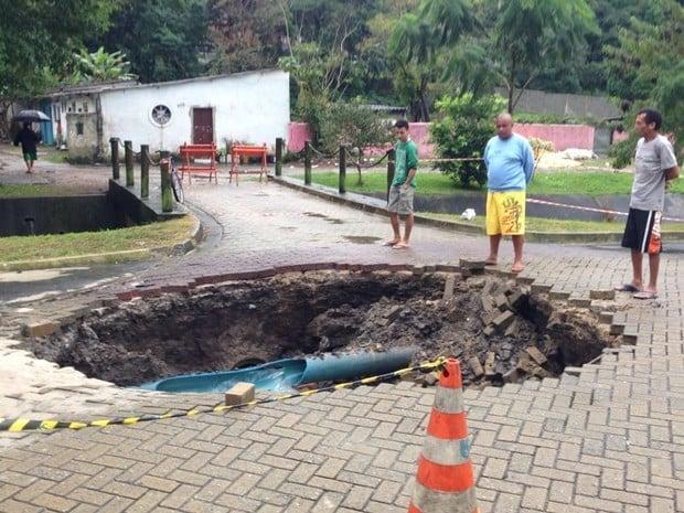 Motorista escapa ileso após asfalto ceder e carro cair em cratera