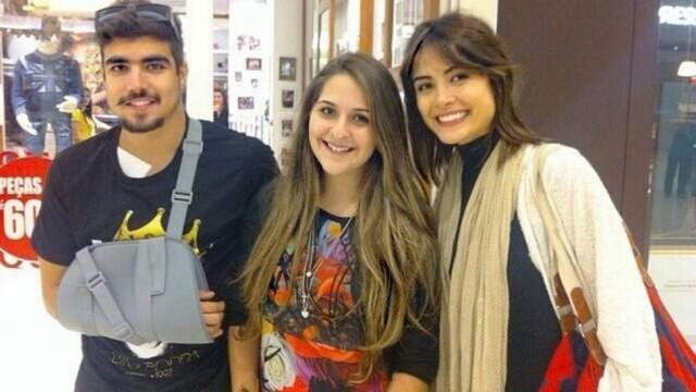 Caio Castro, de tipoia após acidente, e Maria Casadevall posam com fãs em shopping