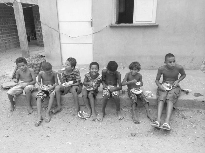 Crianças comendo o que as vezes é a única refeição do dia (Crédito: Reprodução)