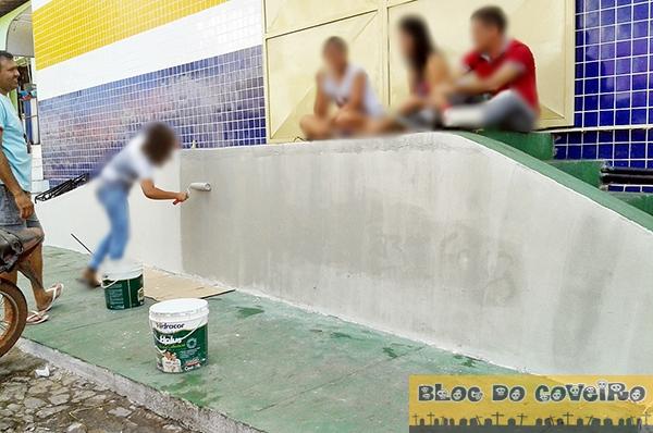 Adolescente passando tinta no muro pichado (Crédito: Reprodução)