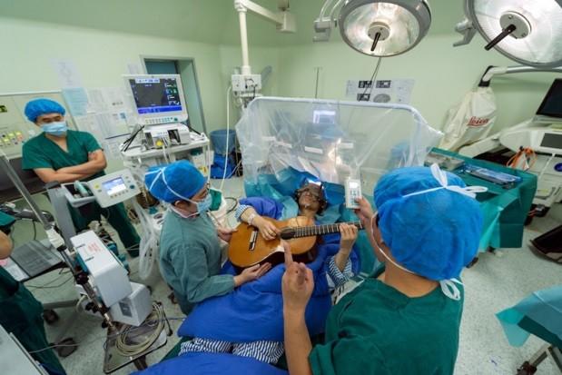 Homem toca violão enquanto faz cirurgia no cérebro (Crédito: Reprodução)