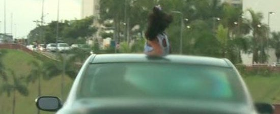 Criança é vista com parte do corpo para fora de carro em movimento