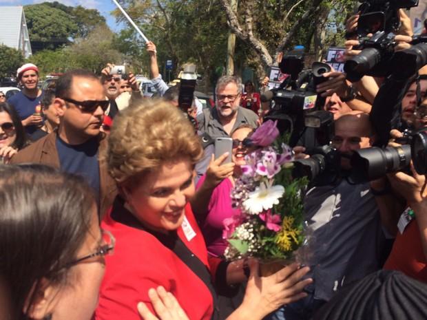 Dilma Rousseff é recebida com flores ao chegar em local de votação (Crédito: Reprodução)