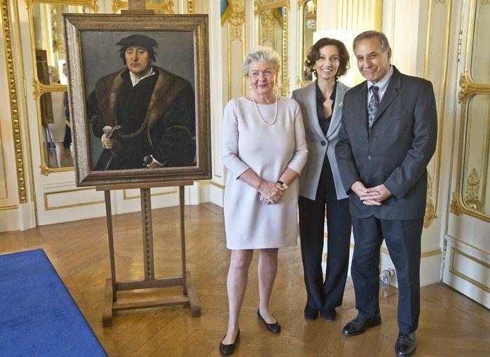 A ministra da Cultura francesa, Audrey Azoulay (centro), posa com Henrietta Schubert e Christopher Bromberg ao lado da pintura de Joos van Cleve em cerimônia no Ministério da Cultura em Paris (Crédito: AFP)