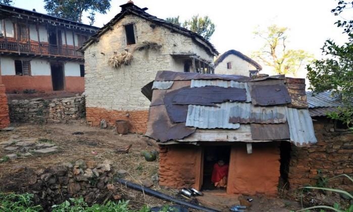 Imagem mostra menina isolada em cabana durante a menstruação, num vilarejo do distrito de Achham, no Nepal   (Crédito: AFP)