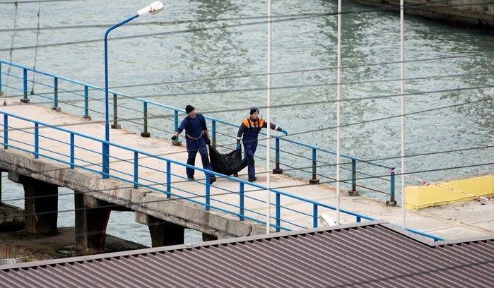 Equipe de emergência carrega bolsa de pástico durante resgate de vítimas e restos do avião miltar russo que caiu no Mar Negro (Crédito: Reuters)