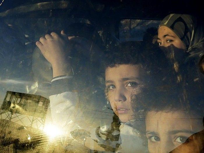 Crianças refugiadas sírias olham através da janela de um carro enquanto cruzam a fronteira do Líbano com suas famílias em Masnaa, no leste do Líbano (Crédito: AP)
