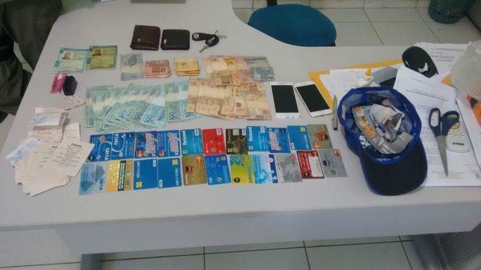 Dinheiro, cartões e celularesa apreendidos com a dupla