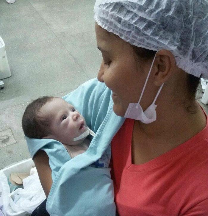 Miguel no colo de sua mãe Olivia Matos (Crédito: Reprodução)