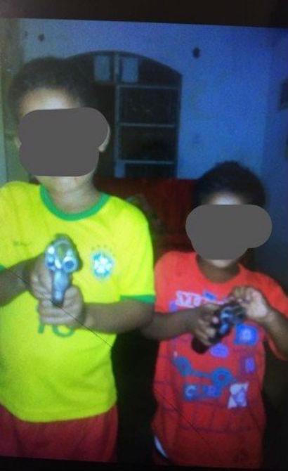 Crianças posam para foto com armas