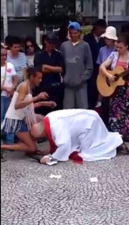Padre beijou pés da transexual Sheila (Crédito: Reprodução/ Youtube)