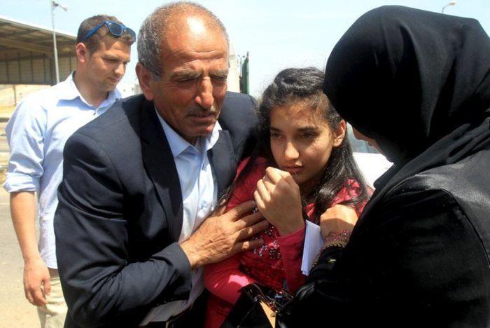 Dima al-Wawi, com os pais, na cidade de Tulkarem, na Cisjordânia, momentos depois de ser libertada  (Crédito: JAAFAR ASHTIYEH/AFP )