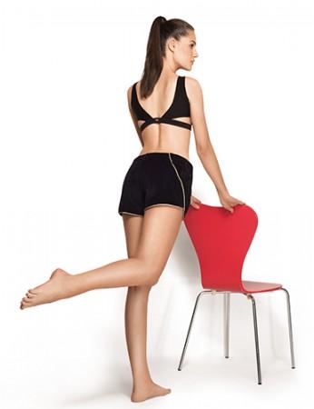 Apoie as mãos em uma cadeira e semiflexione o joelho esquerdo. Eleve o joelho direito e dobre-o para trás, formando um ângulo de 90 graus.