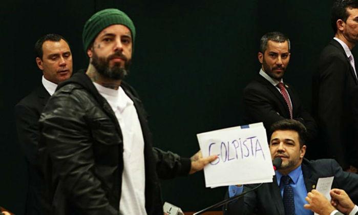 """O cantor Tico Santa Cruz estende cartaz com a palavra """"golpista"""" ao lado do deputado Marco Feliciano (PSC-SP) na Comissão da Cultura da Câmara"""