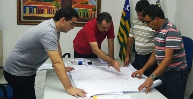 Prefeito e técnicos reunidos visualizam mapa