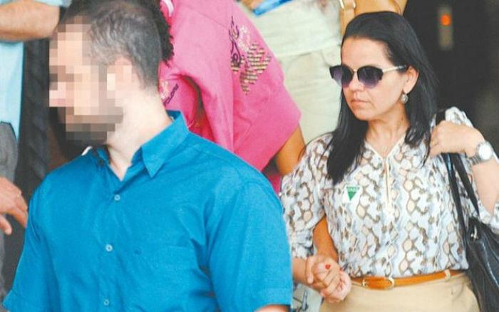 Jovem de 16 anos (com o rosto coberto) deixa delegacia após prestar depoimento sobre caso