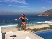 Dani Suzuki usa maiô decotadíssimo e posa em frente a praia no Rio