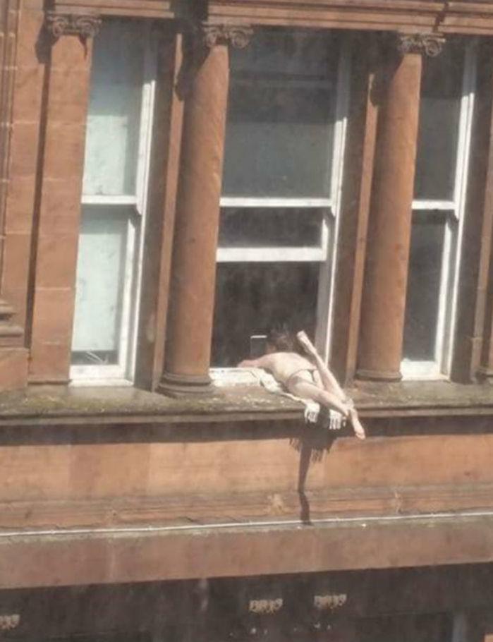 A mulher foi vista somente de biquino pegando sol no parapeito do prédio