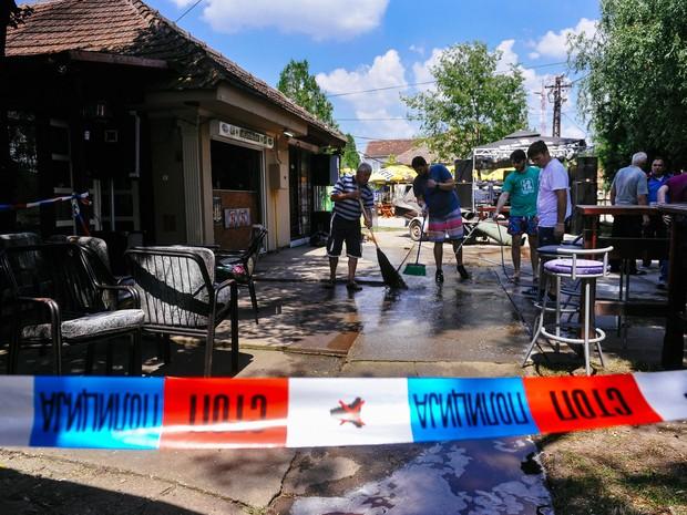 Pessoas lavam a calçada de um café onde um homem matou cinco pessoas em Zitiste, na Sérvia, neste sábado (2) (Crédito: AFP)