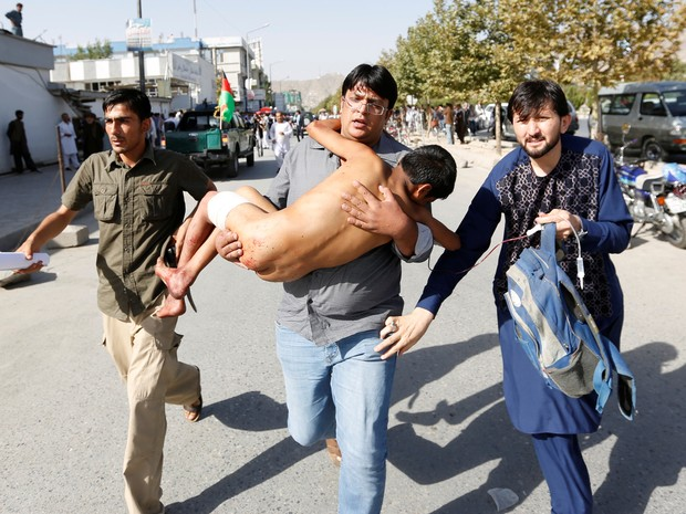 Homem carrega criança nos braços em ataque em Cabul