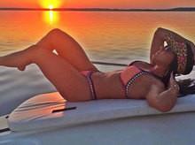 Namorada de Zezé posa em barco de biquíni e diz que está de férias