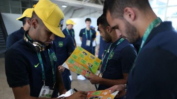 Neymar e Renato Augusto com o álbum da Olimpíada (Crédito: Divulgação/ CBF)
