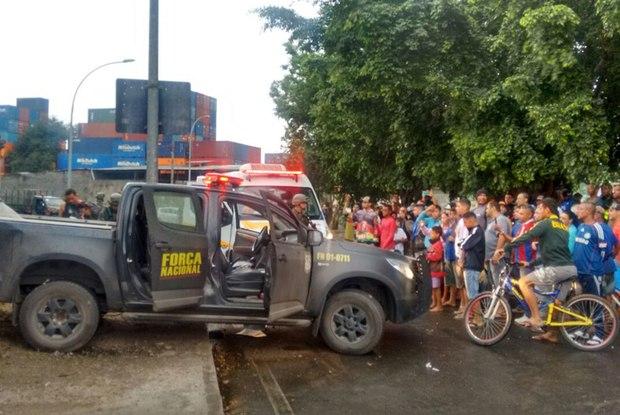 Populares observam carro da Força Nacional atingido na entrada da Favela Vila do João, no complexo de favelas da Maré  (Crédito: Reprodução)