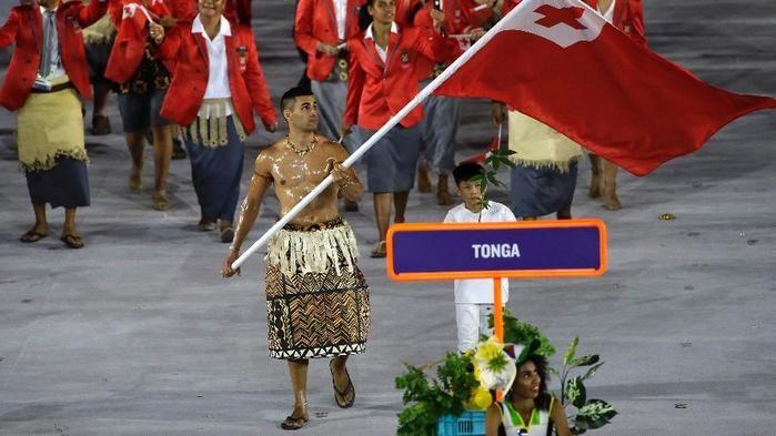 Pita Taufatofua carrega a bandeira de Tonga no desfile das delegações da abertura das Olimpíadas (Crédito: AP)