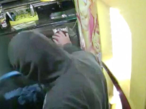 Bandido faz carinho na cabeça de criança (Crédito: Reprodução)
