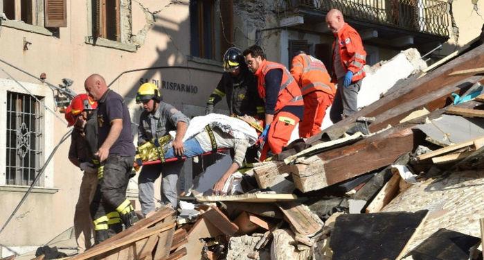 Equipe de resgate retira um homem que ficou soterrado nos escombros  (Crédito: AFP)