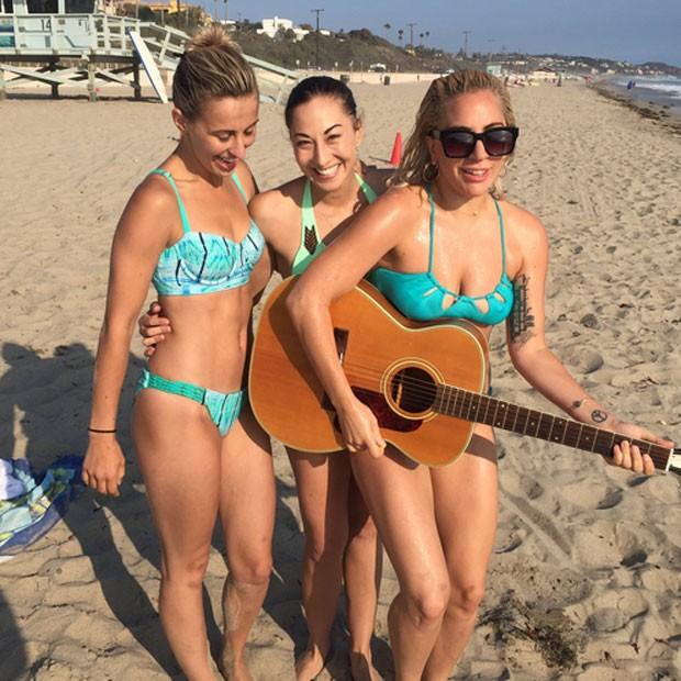 Lady Gaga (à direita) posa de biquíni com amigas em praia (Crédito: Reprodução)