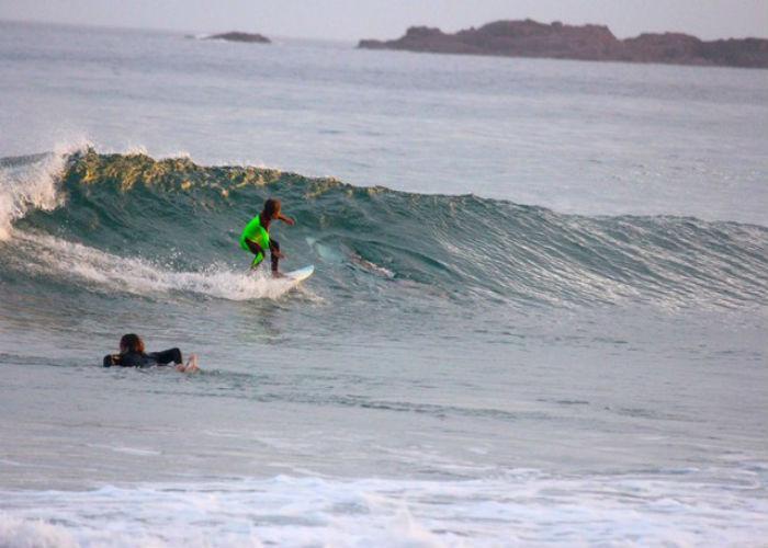 Pai flagra tubarão ao lado do filho ao fotografar criança surfando (Crédito:  Chris Hasson via AP) )