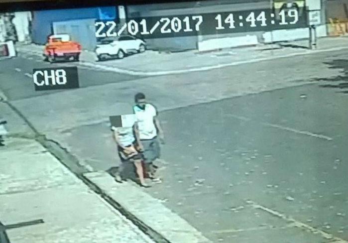 Vítima é obrigada a andar de mãos dadas com criminoso (Crédito: Reprodução)