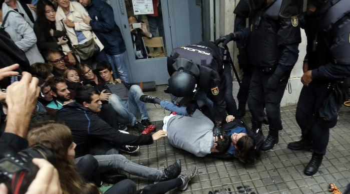 Policiais espanhóis imobilizam duas pessoas do lado de fora de um local de votação em Barcelona, no dia de um referendo que vota a independência da Catalunha  (Crédito: Pau Barrena/AFP)