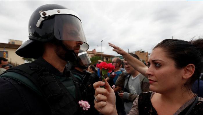 Mulher oferece flor a oficial da Guarda Civil Espanhola após o bloqueio do centro de votação em Sant Julia de Ramis (Crédito: Juan Medina/Reuters)