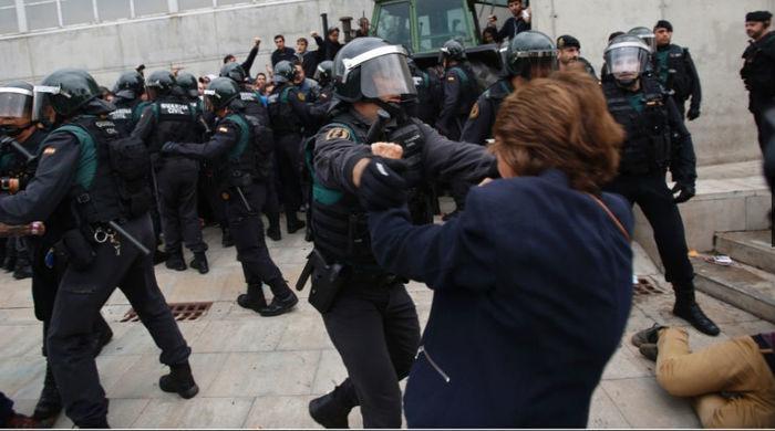 Guarda civil retira separatista que fazia cordão humano em frente a local de votação para garantir a realização do referendo deste domingo  (Crédito: Francisco Seco/AP Photo)