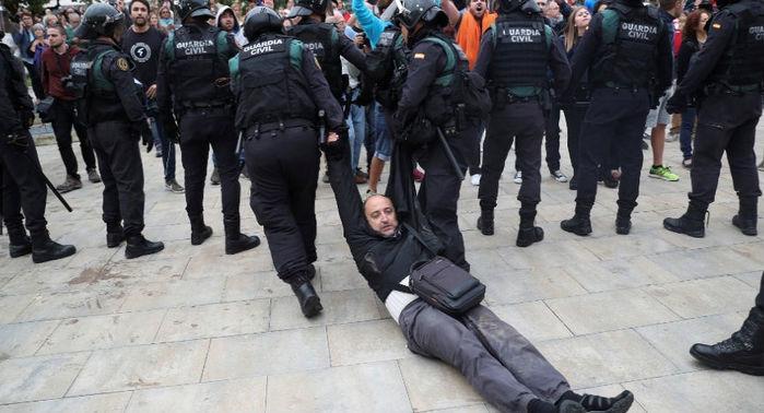 Homem é arrastado por oficiais da Guarda Civil Espanhola no município de Sant Julia de Ramis após fechamento de centro de votação  (Crédito: Albert Gea/Reuters)