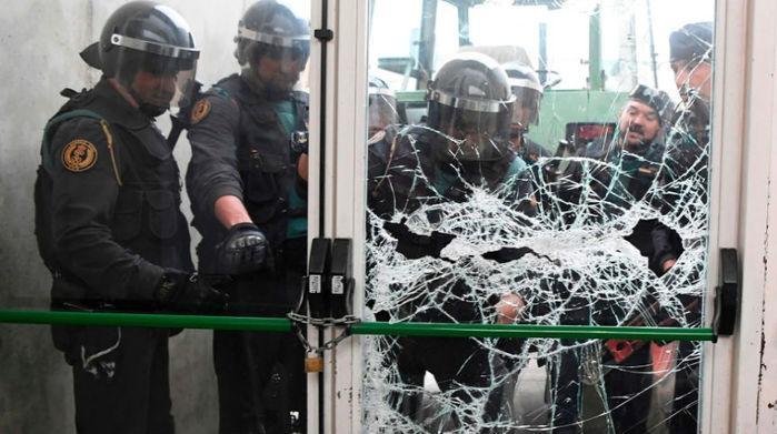 Homens da Guarda Civil Espanhola quebram porta de local de votação no município de Sant Julia de Ramis, onde o presidente catalão votaria na manhã deste domingo (Crédito: Lluis Gene/AFP Photo)