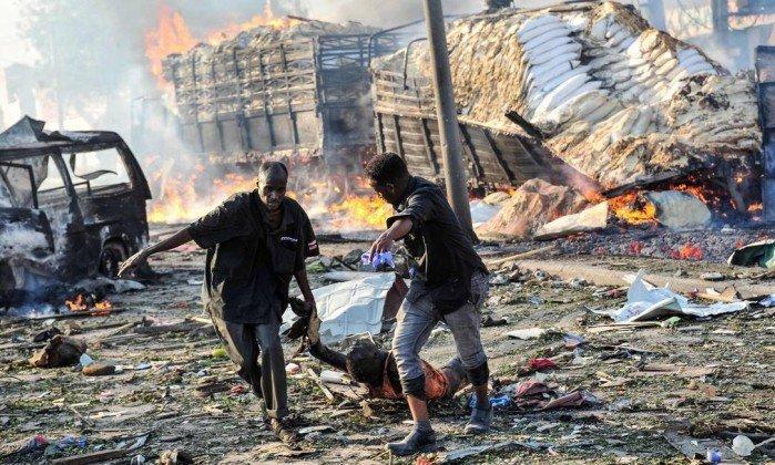 Dois homens arrastam o corpo de uma vítima do bombardeio na capital da Somália (Crédito: MOHAMED ABDIWAHAB / AFP)