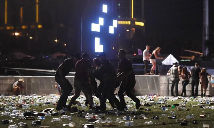 Pessoas ajudam ferido após tiros em Las Vegas  (Crédito: AFP)
