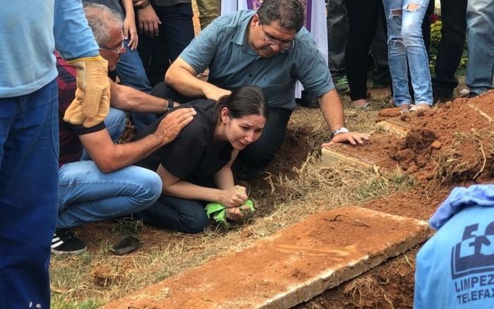 Mãe e pai (à direita) de João Vitor choram ao enterrar o corpo do filho (Crédito: TV Anhanguera )