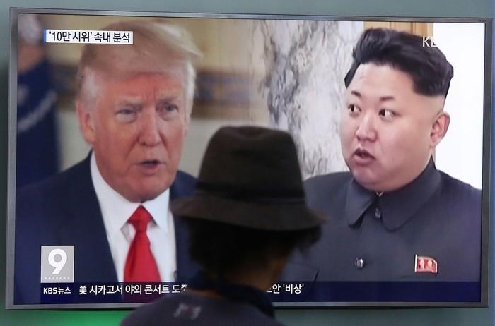 Homem observa imagem do presidente americano, Donald Trump, e do líder norte-coreano, Kim Jong-un, em Seul, na Coreia do Sul  (Crédito: AP)